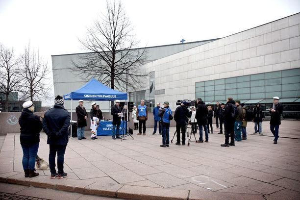 Median edustajat ja tilaisuuden järjestäjät (oikealla) sekä kansa ja koira (vasemmalla) kuuntelemassa vappupäivänä sinisten puheenjohtajan Sampo Terhon puhetta Helsingin Mannerheiminaukiolla.