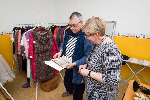 Tea Kekkonen ja Heinolan kaupunginmuseon amanuenssi Sirpa Juuti käyvät läpi kuvia Brita Kekkosesta yhdistääkseen ne oikeiden mekkojen kanssa.