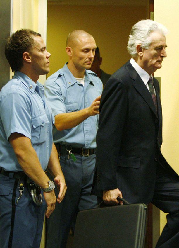Vartijat saattoivat ex-presidentin oikeussaliin kuulemaan syytteensä.