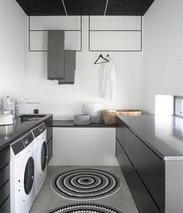 Yläkaapittomuus avartaa tämän kodinhoitohuoneen ilmettä. Katosta roikkuvat kuivaustelineet ovat nerokas valinta, sillä ne toimivat myös sisustuselementteinä.