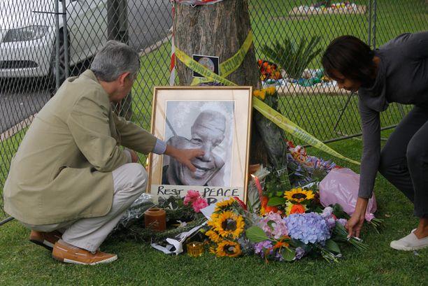 Mandelan talon eteen on jätetty useita kuvia, kynttilöitä ja kukkia.