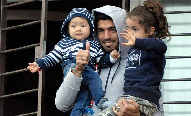Suárez tervehti fanejaan yhdessä lastensa kanssa.