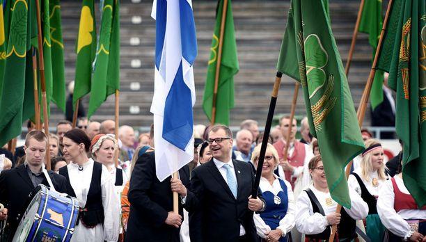 Pääministeri Juha Sipilällä oli hauskaa Suomen lipun taakse piiloutuneen keskustan varapuheenjohtajan Juha Rehulan kanssa puolueen perinteisellä lippumarssilla sunnuntaina Sotkamossa.