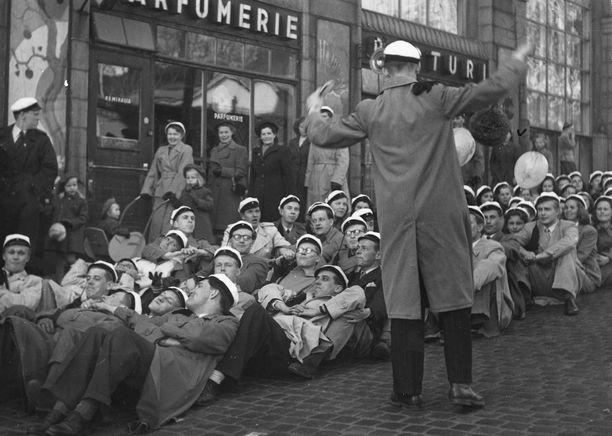 Teekkarit istuutuivat Esplanadikadun kivetykselle odottamaan marssivuoroaan vappuna 1949.