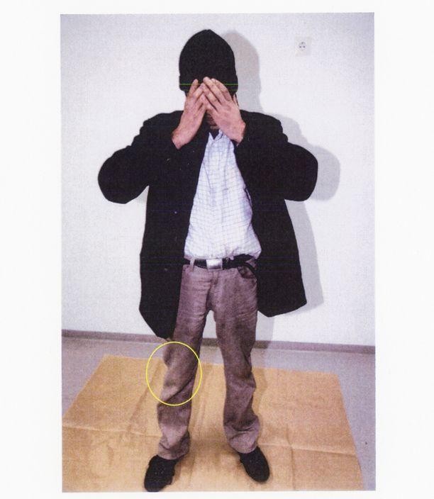 Iqbal kuvattuna Vantaan poliisiasemalla punaisia tahroja housuissaan.