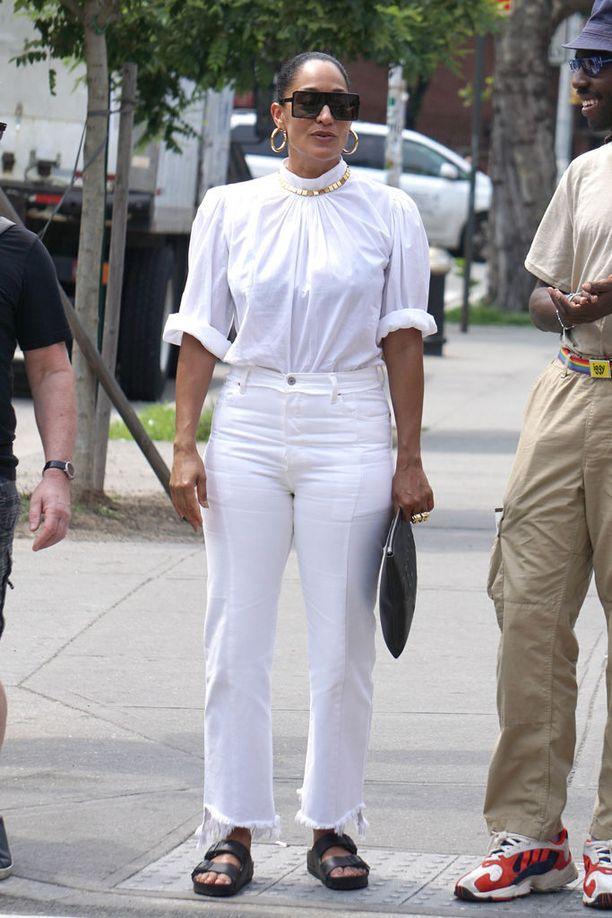 Tracee Ellis Ross käyttää valkoisia farkkuja valkoisen puseron kanssa ja kruunaa tyylin näyttävillä koruilla.