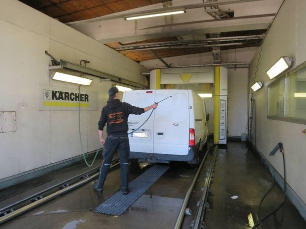 Henkilökunta auttoi pakettiauton esipesussa.
