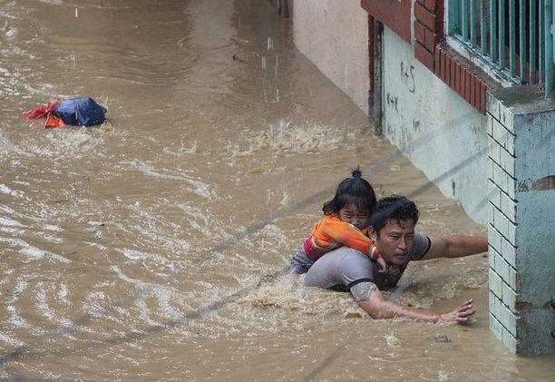 Mies kantaa selässään tytärtään tulvien valtaamassa Nepalin pääkaupungissa Kathmandussa 12. heinäkuuta.