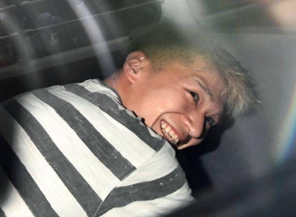 Satoshi Uematsu virnisteli medialle Sagamiharan poliisiaseman edustalla murhattuaan 19 ihmistä.
