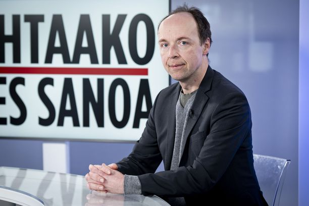 Jussi Halla-aho nauraa demareiden vaalitilaisuusmainokselle.