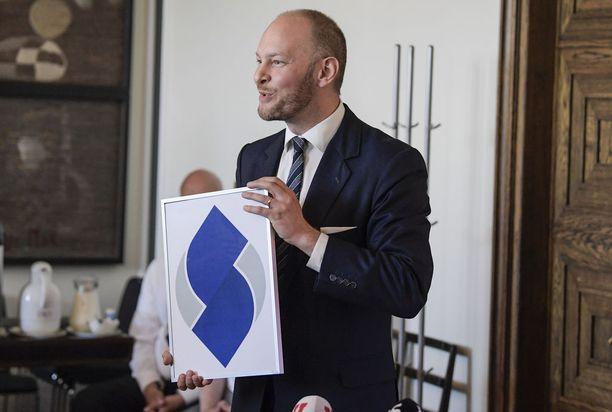 Sinisten puheenjohtaja Sampo Terho esitteli puolueen logoa tiedotusvälineille. Useiden kommentaattoreiden mielestä logo toi mieleen S-ryhmän logon.