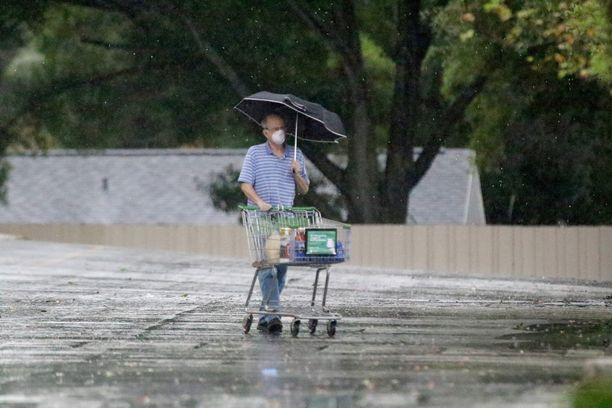 Yhdysvaltalaismies suojautui sateelta torstaina. Kuvituskuva