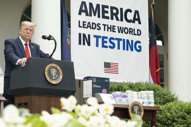 Tällaisten plakaattien edessä Trump on jo aiemmin esiintynyt Valkoisessa talossa. Banderollin väite on osittain oikein.