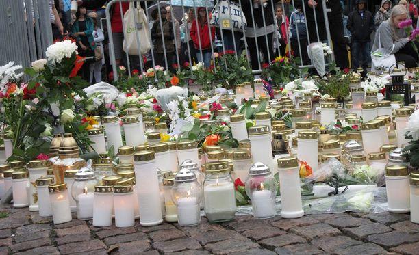 Ihmiset ovat laskeneet kukkia ja kynttilöitä Turun Kauppatorille.
