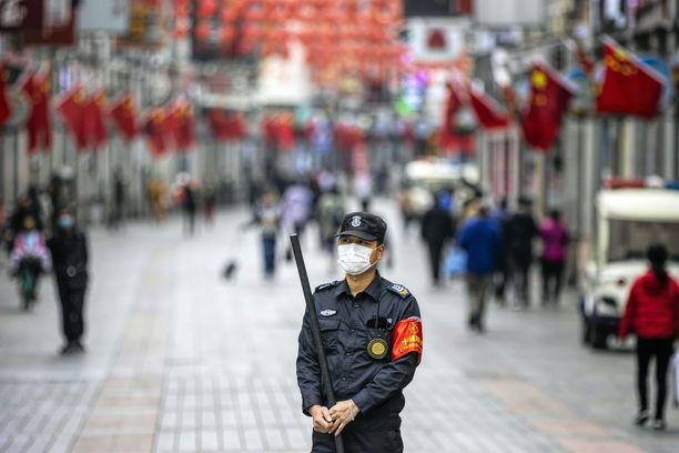 Turvamies seisoo ostosalueen edessä Guangzhoussa Guangdongin maakunassa Kiinassa. Julkisilla paikoilla vaaditaan hengitysmaskin käyttöä.