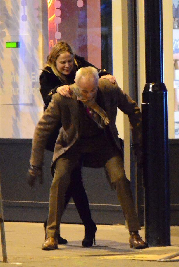 Naisystävä yrittää kiivetä Andrew Ridgeleyn selkään.