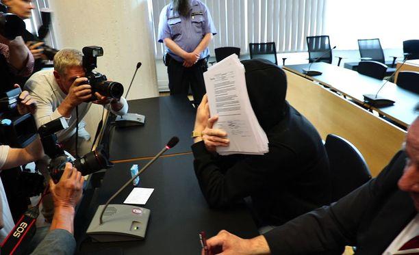 Michael Penttilä peitti kasvonsa saapuessaan oikeudenkäyntiin.