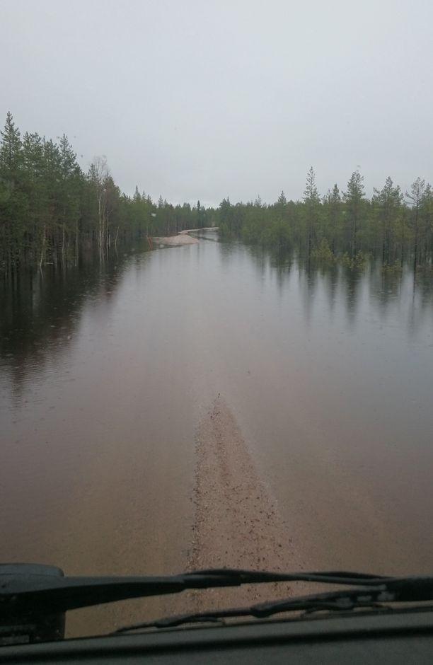 Pudasjärven Petäjäkankaantie oli vielä perjantaina aamulla näkyvissä, mutta iltapäivällä tulva oli hukuttanut tien lähes täysin.
