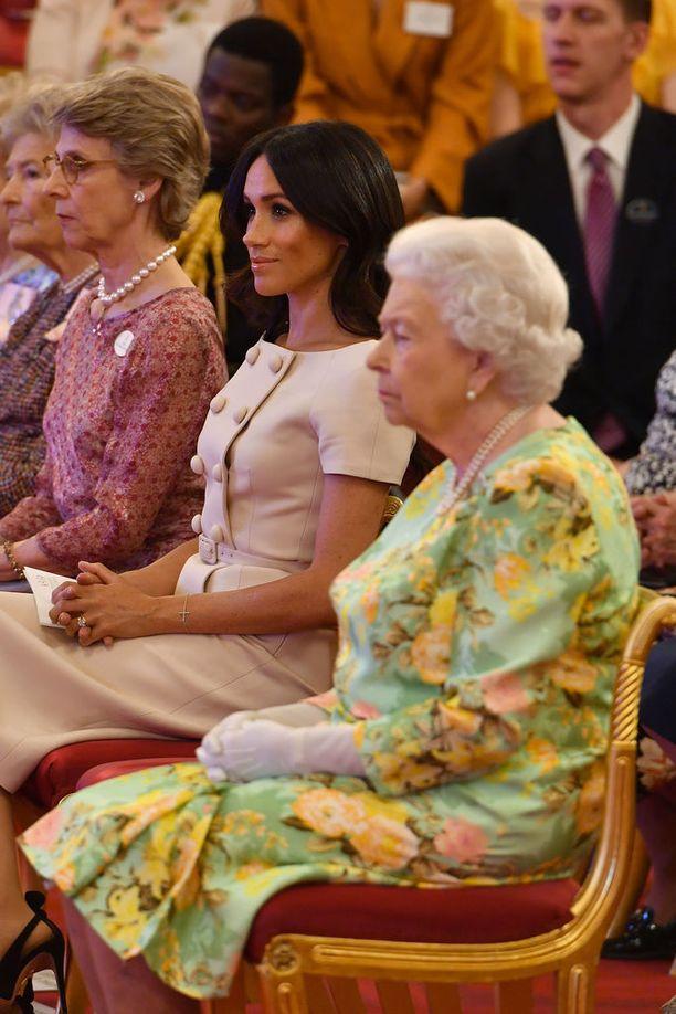 Meghan istuu selkä suorana jäljitellen kuningattaren muodollista ja eleganttia asentoa. Kaksikko edusti yhdessä tällä viikolla Buckinghamin palatsissa pidetyssä Young LeaderŽs Awards -seremoniassa.