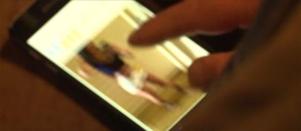 Poliisin agentti tutki prostituutioilmoitusta matkapuhelimella.