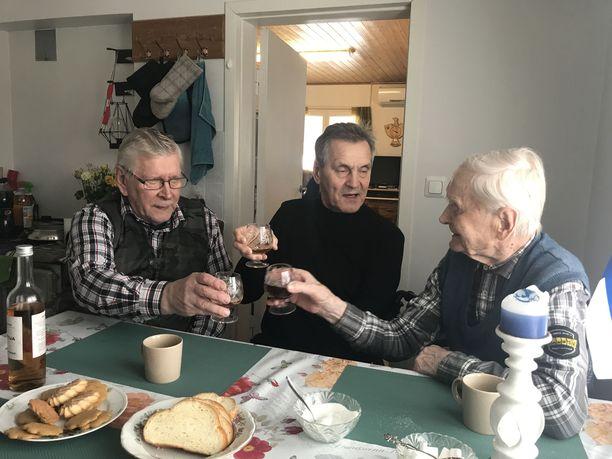 """Tauno Tikkanen otti """"näkäräiset"""" kiuruvetisen keksijä Aulis Kärkkäisen (keskellä) 103-vuotiassyntymäpäivälahjaksi tuomaa leikattua konjakkia poikansa Tenhon (vas.) kanssa. Edellisen kerran Tauno otti leikattua konjakkia Marskin 75-vuotispäivän kunniaksi sotarintamalla 4.6.1942."""