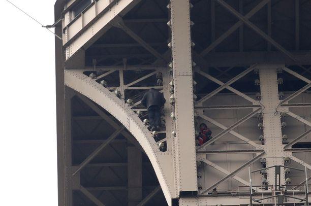 Tuntematon mies kiipieli maanantai-iltana Pariisin Eiffel-tornissa.