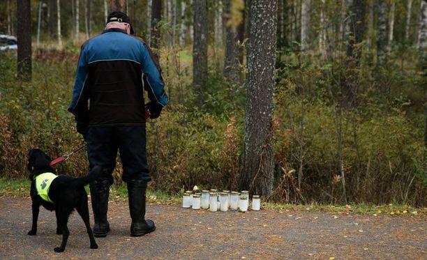 Kuvan mies löysi uhrin puun juuresta makaamassa ollessaan ulkoiluttamassa koiraa. Lompakko oli uhrin vieressä ja kortit oli levitetty.