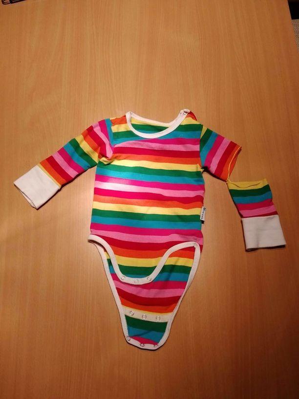 Tästä äitiyspakkauksen bodystä irtosi hiha, kun äiti riisui vaatteen vauvan päältä. Toinen äiti kertoo omana kokemuksenaan, että viime vuoden pakkauksessa olleista vaatteista irtosi neppareita.