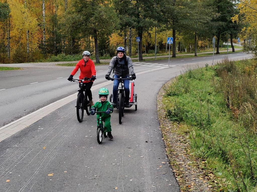 Jyväskyläläisen perheen vanhemmat polkevat sähköpyörällä. Kuvassa yksivuotias on kärryssä ja kolmevuotias liikkuu potkupyörällä.