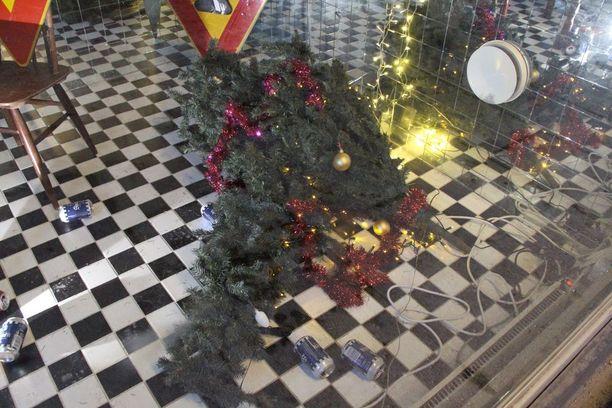Teoksessa on myös kaatunut joulukuusi ja oluttölkkejä
