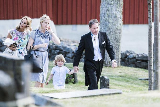 Chris piteli poikaansa kädestä saapuessaan kirkkoon.