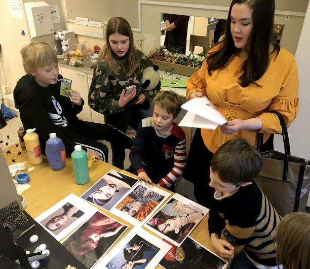 Ninja Sarasalo ja lapset katselivat, millaisia töitä Ninja on tehnyt mallivuosinaan.