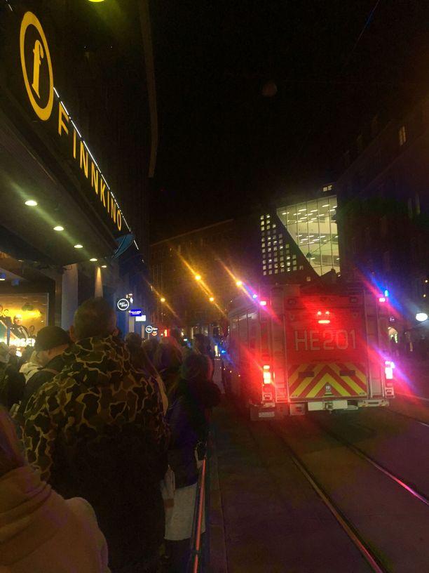 Yleisöä elokuvateatterin ulkopuolella perjantaina, palokunta tarkastamassa kohdetta.