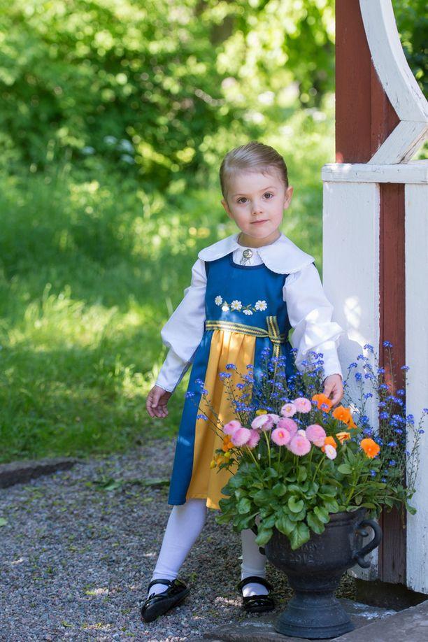 3-vuotias Estelle poseeraa kansallispuvussa yllättävän totisena.