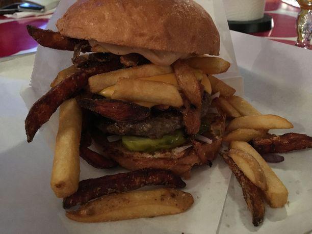 Sami Hedberg osallistui tämän annoksen kehittelyyn. Tuhdin burgerin sisällä on pihvin lisäksi nyhtöpossua ja ranskalaisia perunoita.