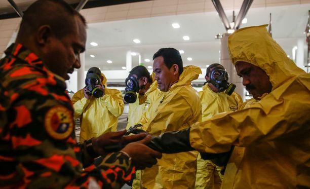 Lentokenttää vaarallisten aineiden varalta tutkimut ryhmä pukeutui suojapukuihin ennen tutkimuksen aloittamista.