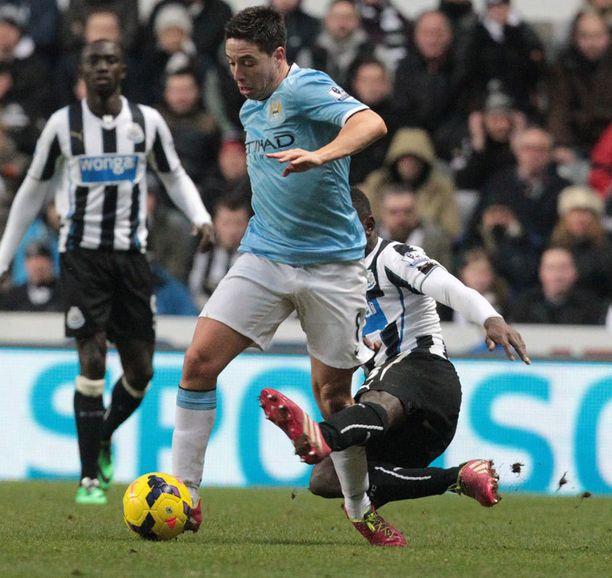 Manchester Cityn Samir Nasrin polvi vääntyy, kun Newcastlen Mapou Yanga-Mbiwan viikate heilahtaa.