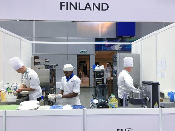 Suomen kilpailukeittiössä Mikko Pakola (vas.) ja Kristian Vuojärvi. Keskellä avustaja huolehtimassa tarjoiluastioista.