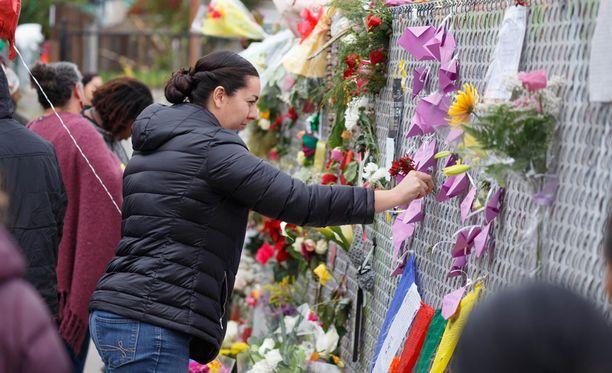Ihmiset toivat kukkia ja kynttilöitä varastorakennuksen lähelle Kalifornian Oaklandissa.