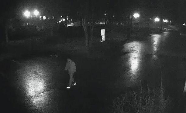 Valvontakameran infrapunakuvatallenne näyttää, kuinka ulkoiluasuun sonnustautunut mies kävelee rauhallisesti naisen laukku vasemmassa kädessään.