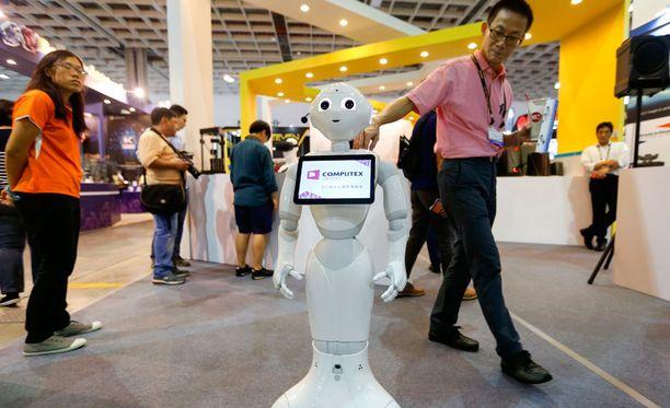 Vierailija koskettaa Pepper-robottia messuilla Taiwanissa.