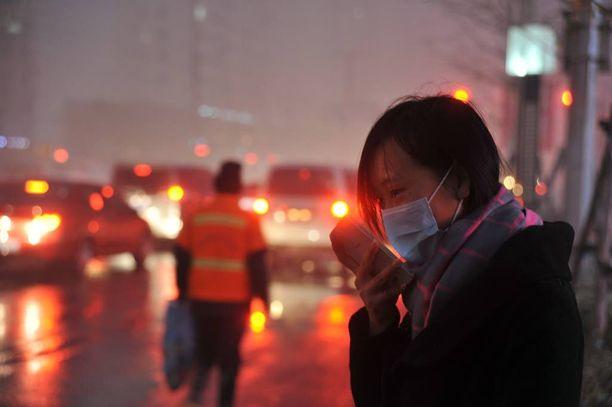 Nainen käytti eilen kasvosuojusta Shenyangissa Kiinassa.