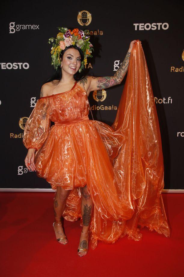 Veronica Verho luotti gaalahumussa persoonalliseen, oranssiin ja hieman läpikuultavaan mekkoon sekä kauniiseen kukkakoristeluun hiuksissaan.