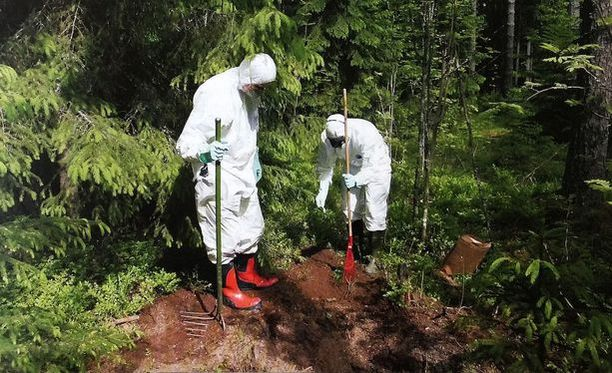 Poliisit tutkimassa metsähautaa, mihin uhri oli haudattu.