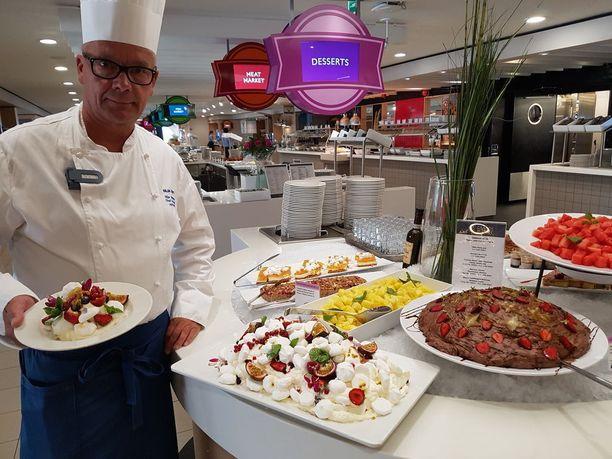 Keittiöpäällikkö Jyrki Tulkki esittelee buffet-pöydän kaunotarta eli marjapavlova-jälkiruokaa marjoista, marengista ja kermasta.