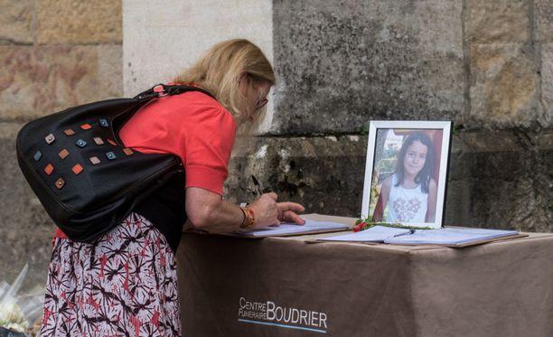 Nainen kirjoittaa surunvalittelua uhrin omaisille.