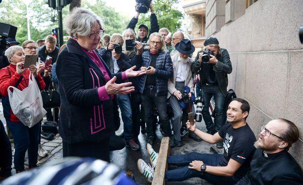 Piispa Irja Askola tuli tapaamaan protestiaan jalkapuussa tuomiokapitulin ulkopuolella istunutta Sadinmaata.
