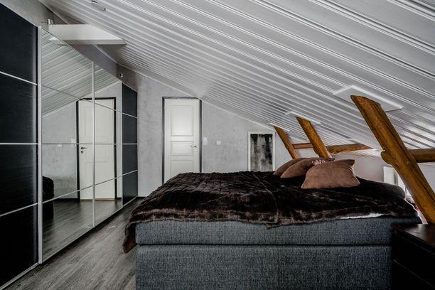 Makuuhuoneessa on tunnelmallinen vinokatto. Moderni sisustus tuo särmää puutalokotiin.