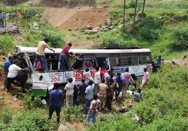 Ihmiset yrittivät auttaa bussiturman uhreja Sanivarampetin kylässä Jagtialin alueella.