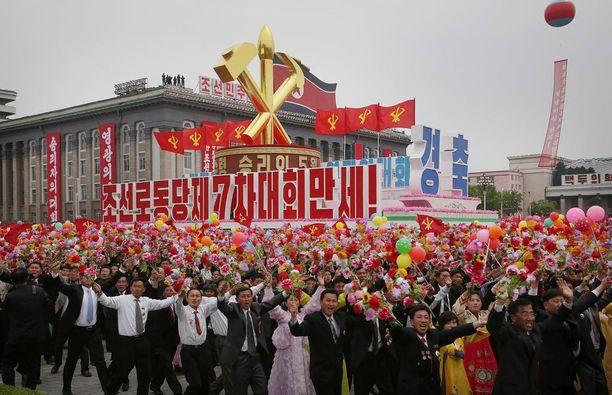 Pohjoiskorealaiset marssivat Korean työväenpuolueen symboleiden kanssa Kim Il-sungin aukiolla Pjongjangissa tiistaina.